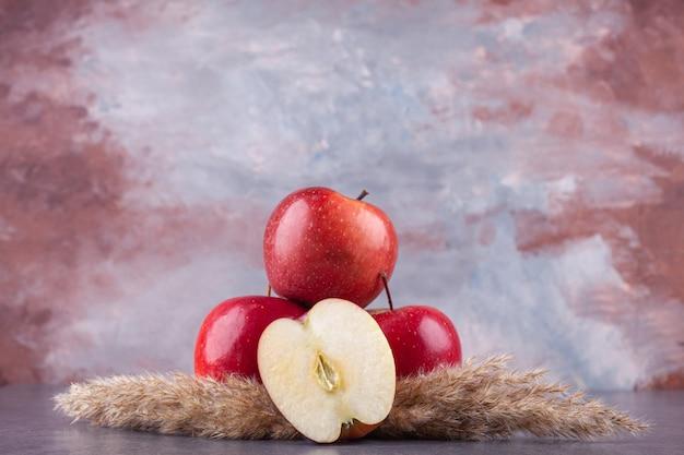 Délicieuses pommes rouges mûres placées sur du marbre.