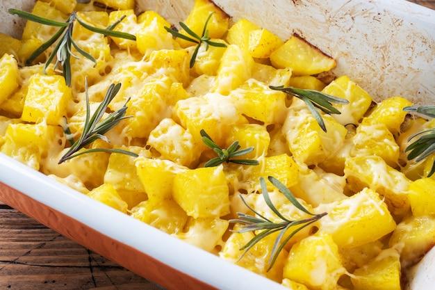 De délicieuses pommes de terre au four avec du fromage aux épices et du romarin dans une plaque de cuisson en céramique sur un fond rustique en bois. fermer