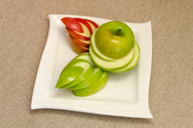 Délicieuses pommes tranchées sur une assiette blanche