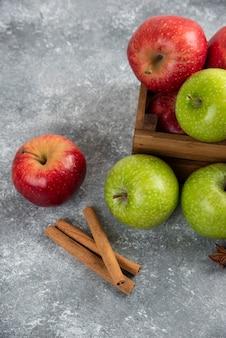 De délicieuses pommes vertes et rouges entières dans une boîte en bois.
