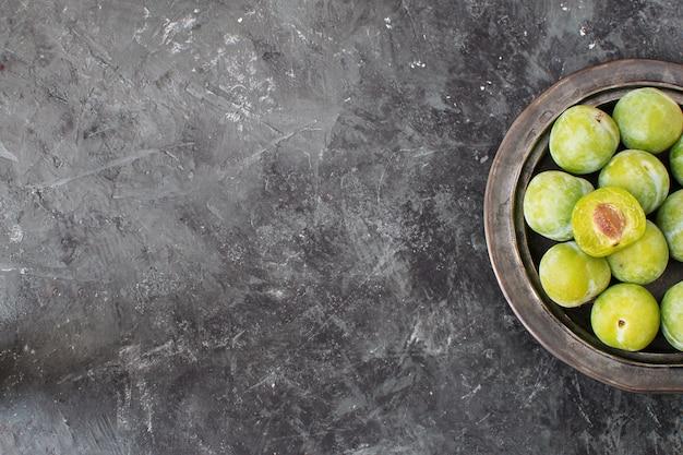 Délicieuses prunes vertes mûres greengages sur plaque noire en céramique