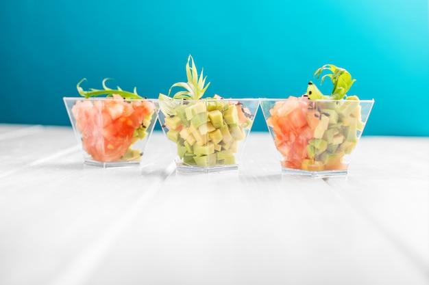 Délicieuses salades à l'avocat et à la tomate dans des tasses.