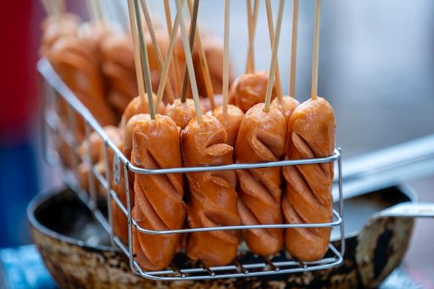De délicieuses saucisses de viande grillée dans des bâtons de bois au marché de l'alimentation de rue dans la vieille ville de hanoi, vietnam. fermer