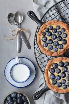 Délicieuses tartelettes aux bleuets avec crème à la vanille et béton gris