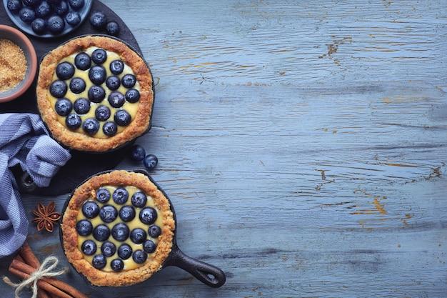 Délicieuses tartelettes aux bleuets avec crème à la vanille sur le bl