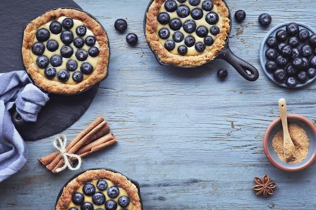 Délicieuses tartelettes aux bleuets avec crème à la vanille sur bois rustique clair