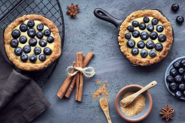 Délicieuses tartelettes aux bleuets avec crème à la vanille sur une surface texturée foncée