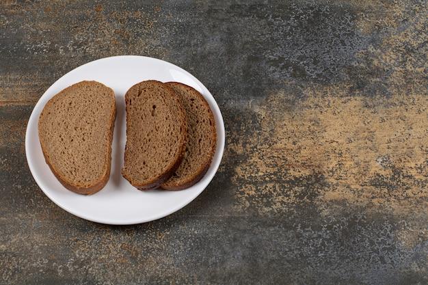Délicieuses tranches de pain sur plaque blanche