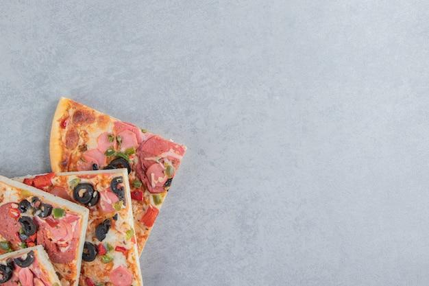 Délicieuses tranches de pizza empaquetées sur du marbre