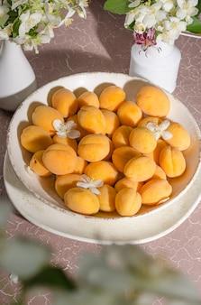 Délicieux abricots mûrs dans un bol sur fond beige