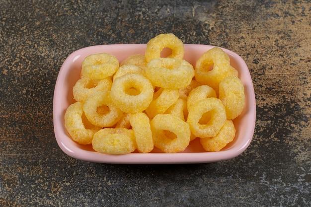Délicieux anneaux de céréales dans un bol rose.
