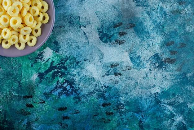 De délicieux anneaux de maïs dans une assiette, sur la table bleue.