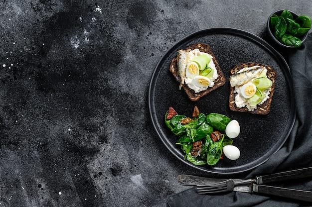 Délicieux apéritif avec des œufs à la coque et des sandwiches de sardines en conserve