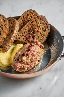 Délicieux apéritif, steak tartare de bœuf sauce jaune et pain de seigle, servi dans une assiette en cuivre sur marbre