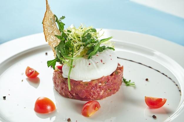 Délicieux apéritif - tartare de boeuf avec croûtons, œuf poché et salade de roquette dans une assiette blanche sur nappe bleue