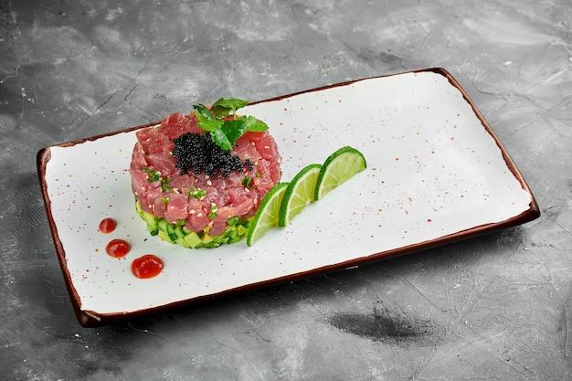 Délicieux apéritif - tartare de thon à l'avocat et caviar noir sur une plaque blanche sur une table grise.