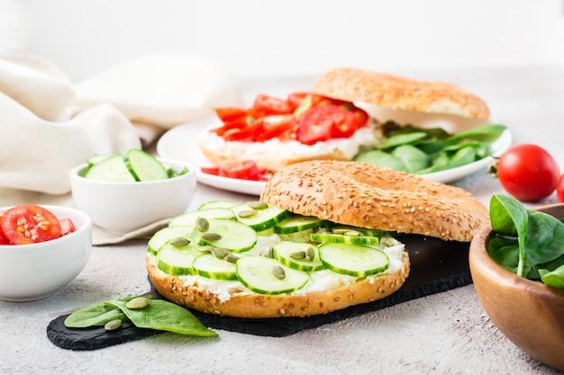 Délicieux bagel farci de feta, de graines de concombre et de citrouille et de feuilles d'épinards sur une ardoise. collation santé légère et vitaminée
