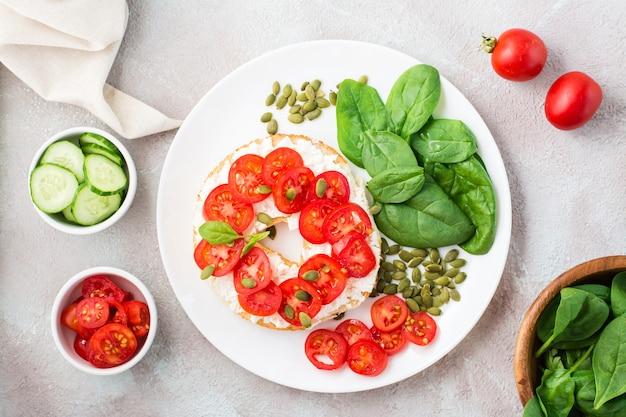 Délicieux bagel farci de feta, tomates et graines de citrouille et feuilles d'épinards sur une assiette. snack vitaminé léger et sain. vue de dessus