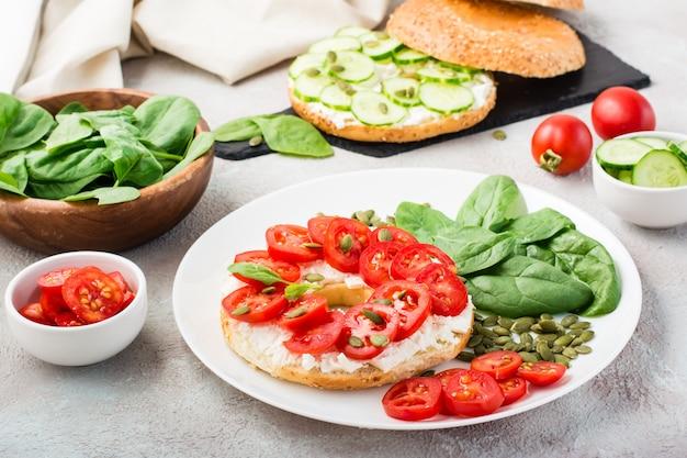 Délicieux bagel farci de feta, tomates et graines de citrouille et feuilles d'épinards sur une assiette. snack vitaminé léger et sain