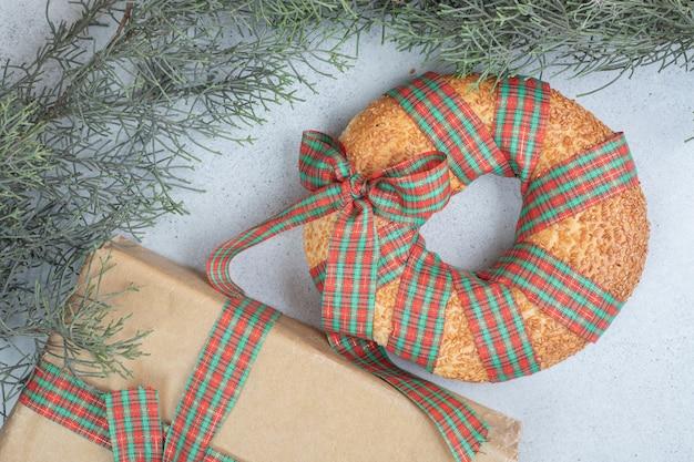 Délicieux bagel sucré noué dans un arc festif avec un cadeau de noël