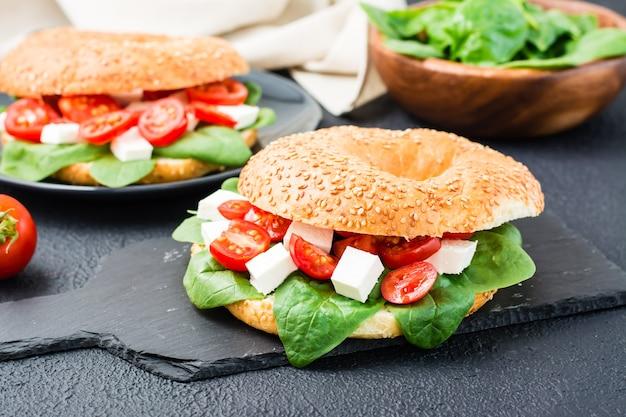 De délicieux bagels prêts à manger farcis de tomates, de feta et de feuilles d'épinards sur fond noir. collation légère et saine