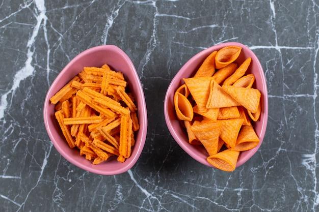 Délicieux bâtonnets croustillants et chips triangulaires dans des bols roses.