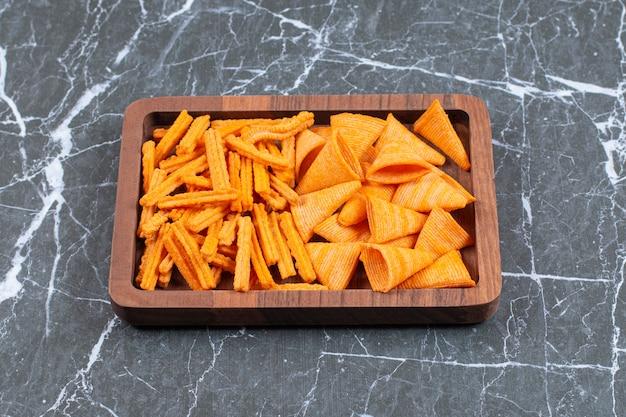 Délicieux bâtonnets croustillants et chips triangulaires sur plaque de bois.
