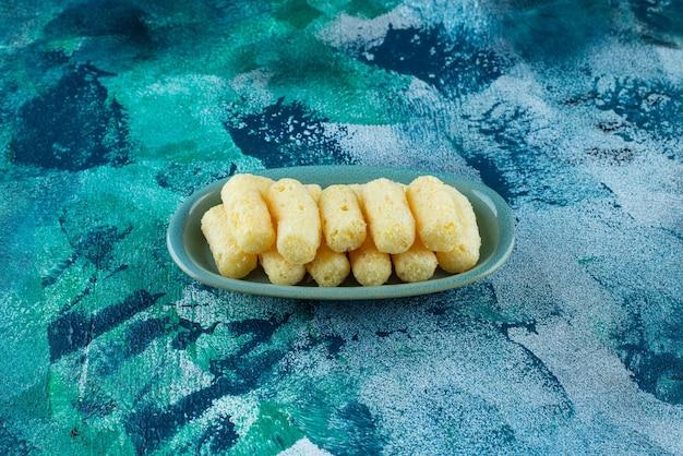 Délicieux bâtonnets de maïs sucré dans une assiette sur bleu.