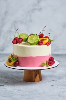 Délicieux et beau gâteau fait main. confiserie pour les vacances. le dessert est garni de framboises fraîches, de cerises, de limes et d'abricots.