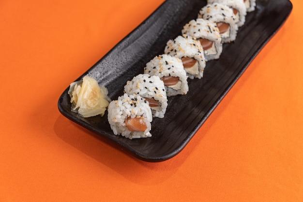 Délicieux et beaux sushis sur la table orange