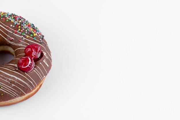 Un délicieux beignet au chocolat entier placé sur une table blanche.