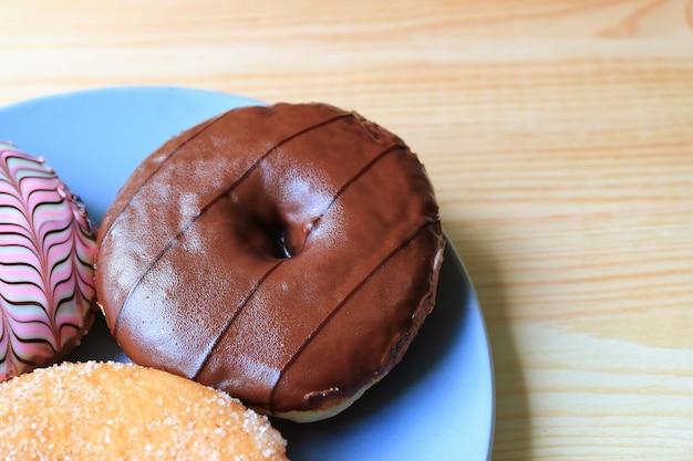 Délicieux beignet au chocolat noir avec deux autres faveurs différentes sur une assiette bleue servie sur une table en bois