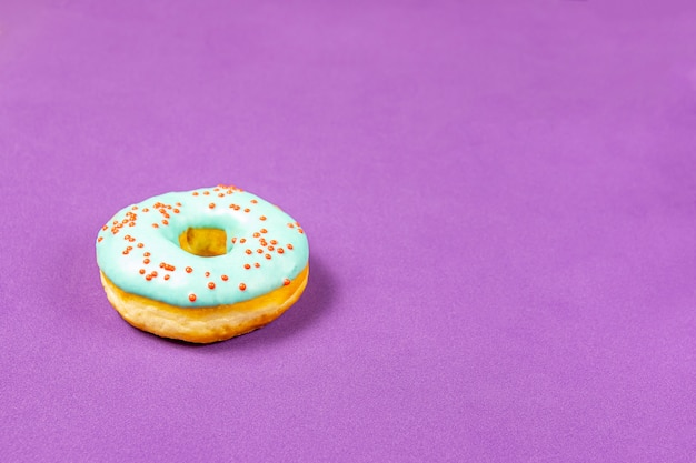 Délicieux beignet avec glaçage bleu et saupoudrer de gros plan sur une table violette. concept de nourriture sucrée (dessert).