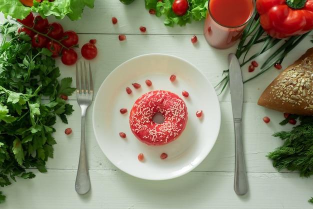 Un délicieux beignet se trouve sur une assiette et mange pour le manger. problèmes de bonne nutrition et concept de choisir entre des aliments sains et non sains