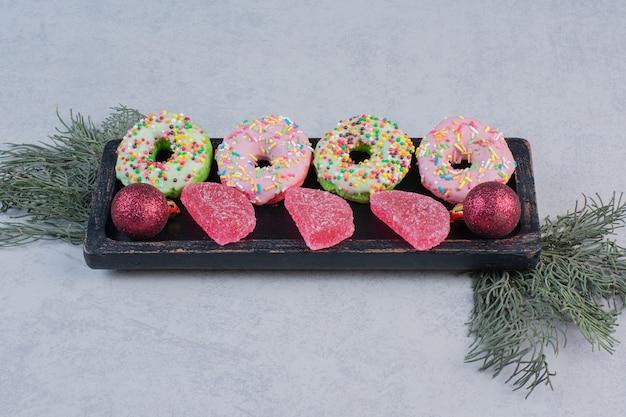 Délicieux beignets avec arroseurs et marmelades sur plaque noire.