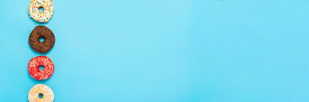 Délicieux beignets de différents types sur une surface bleue. concept de bonbons, boulangerie, pâtisseries. . mise à plat, vue de dessus