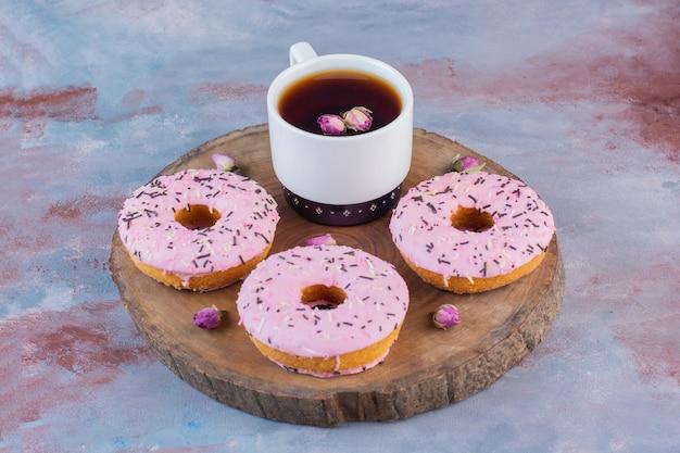 Délicieux beignets avec glaçage rose et une tasse de thé noir