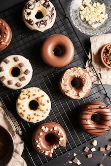 De délicieux beignets recouverts de glaçage au chocolat blanc et brun avec les ingrédients sur une table