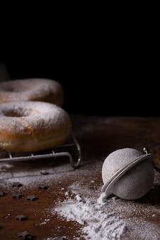 Délicieux beignets avec sucre en poudre et tamis