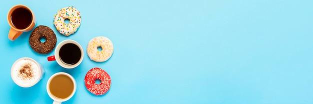 Délicieux beignets et tasses avec boissons chaudes, café, cappuccino, thé sur une surface bleue. concept de bonbons, boulangerie, pâtisseries, café, réunion, amis, équipe amicale. mise à plat, vue de dessus