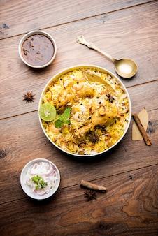 Délicieux biryani au poulet épicé dans un bol sur fond de mauvaise humeur, c'est une cuisine indienne et pakistanaise populaire