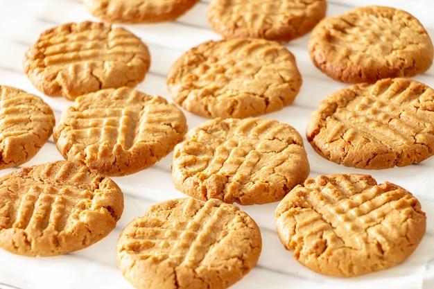 De délicieux biscuits au beurre d'arachide faits maison sur une grille de refroidissement. espace en bois blanc. concept de collation saine.
