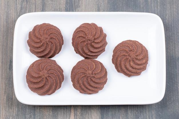 Délicieux biscuits au cacao sur plaque blanche