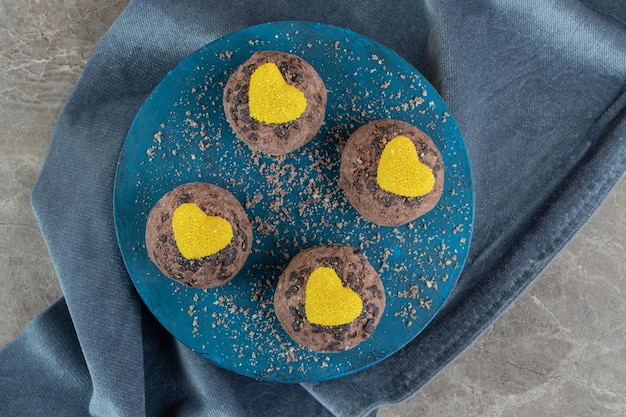 Délicieux biscuits au chocolat avec marmelades sur tableau bleu
