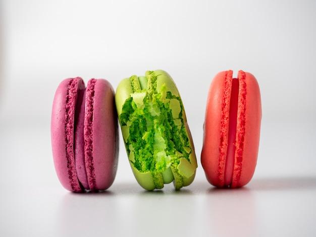 Délicieux biscuits aux amandes colorés et lumineux sur fond blanc. l'un d'eux est mordu. vue de côté