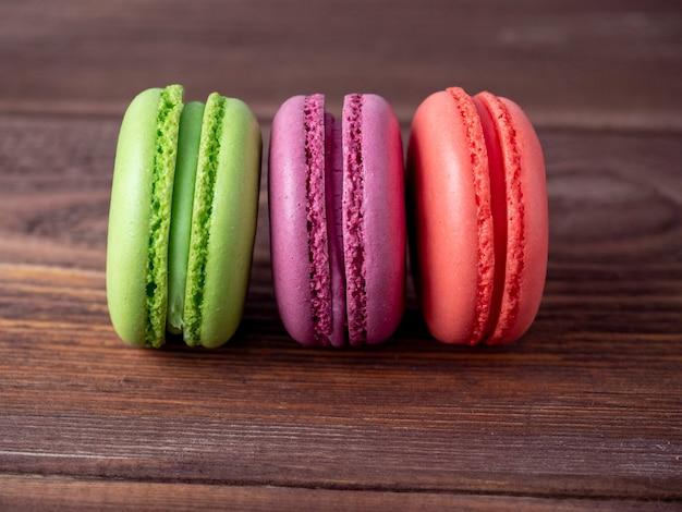 De délicieux biscuits aux amandes douces de différentes couleurs sur un fond en bois marron. vue de côté