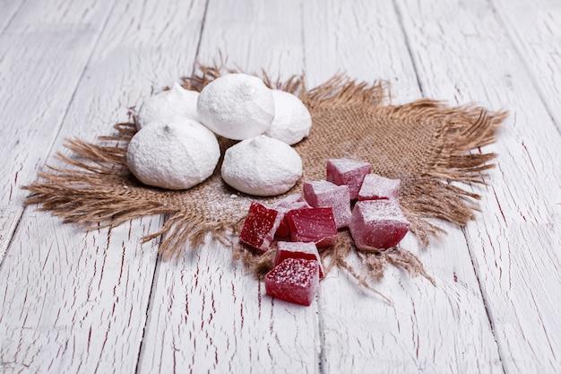 Délicieux biscuits blancs et rouges pour le thé servi sur une table en bois blanc