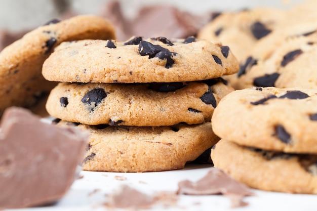 Délicieux biscuits à la farine de blé et gouttes de chocolat à l'intérieur de la pâte sablée préparée, biscuits faits maison de forme irrégulière ronde ou ovale pliés ensemble