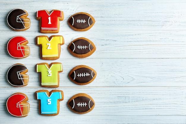 De délicieux biscuits en pain d'épice décorés de signes de football sur bois blanc