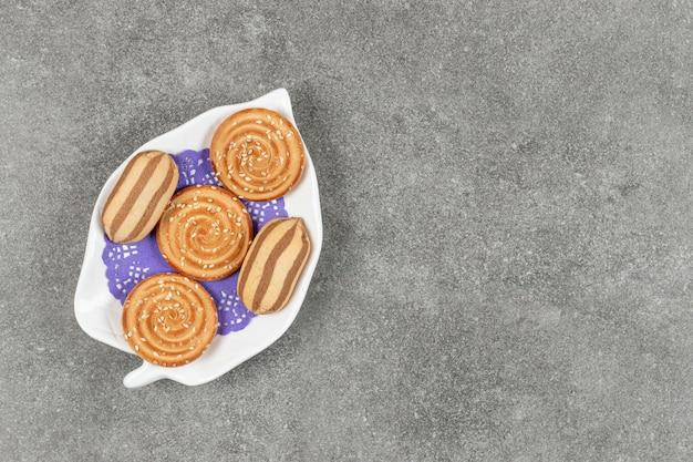 Délicieux biscuits à rayures au chocolat et biscuits au sésame sur plaque blanche